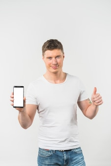 Smiling young man showing thumb up sign showing smart phone against white background