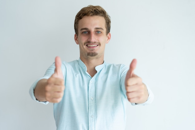 Smiling young man showing thumbs up and looking at camera.