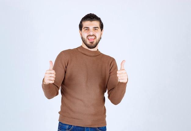 Улыбающийся молодой человек показывает палец вверх на белой стене.