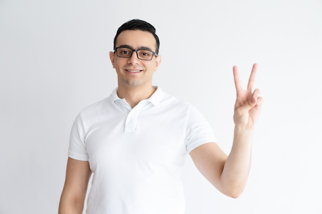 Smiling young man showing victory sign and looking at camera.