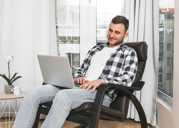 Smiling young man sitting on chair using mobile phone at home