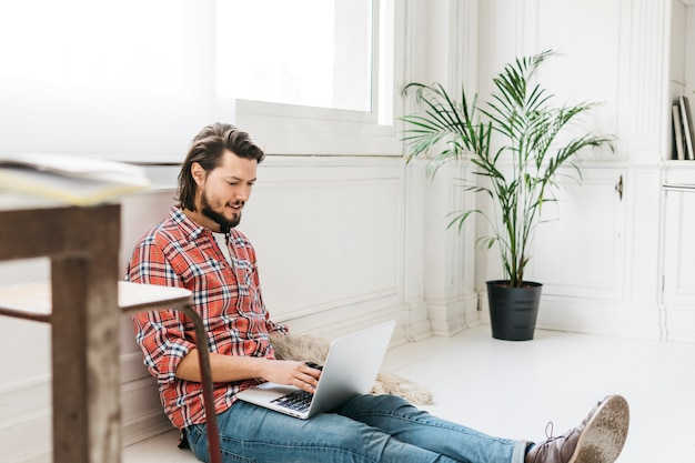 Smiling young man sitting at home using laptop