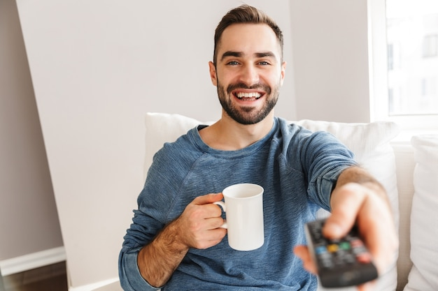 自宅のソファに座って、テレビのリモコンを持って、コーヒーを飲みながら、笑顔の若い男