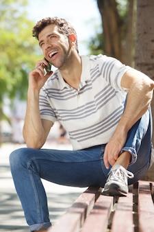 屋外でベンチに座って携帯電話で話す若い男に笑顔