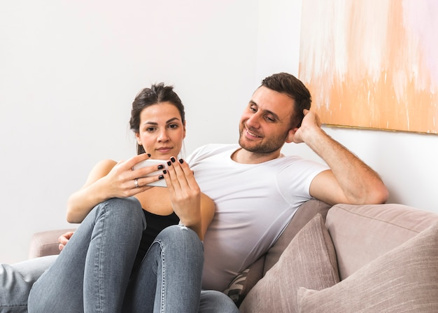 Smiling young man sitting on sofa looking at her girlfriend using mobile phone