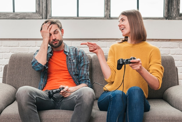 Smiling young man sitting on sofa teasing her boyfriend holding joystick after winning the video game