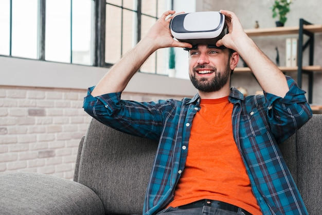 Smiling young man sitting on sofa wearing virtual reality camera