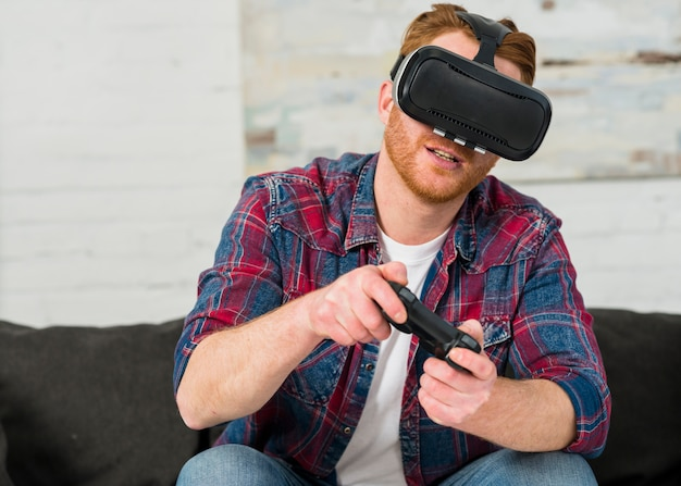 Smiling young man sitting on sofa wearing virtual reality glasses playing with joystick