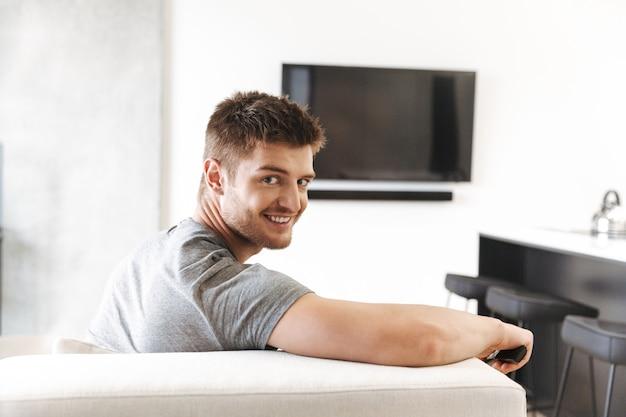 テレビのリモコンで座っている笑顔の若い男