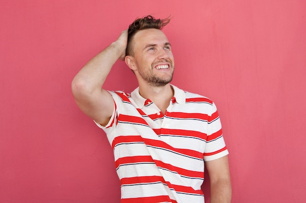 Smiling young man smiling against red wall with hand in hair