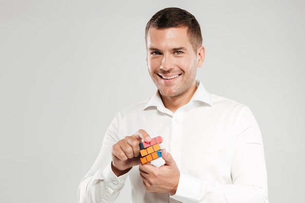 Smiling young man solve rubik's cube.