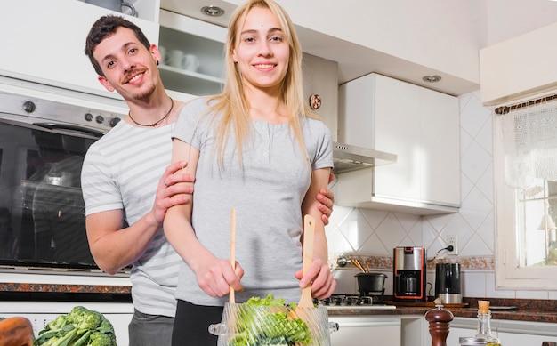 부엌에서 야채를 준비하는 젊은 여자 뒤에 서있는 젊은 남자 미소