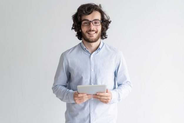 Smiling young man standing and holding tablet computer