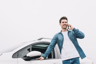 Smiling young man standing in front of car talking on smartphone