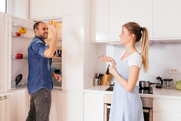 Smiling young man standing near the open refrigerator throwing vegetable in his wife's hand