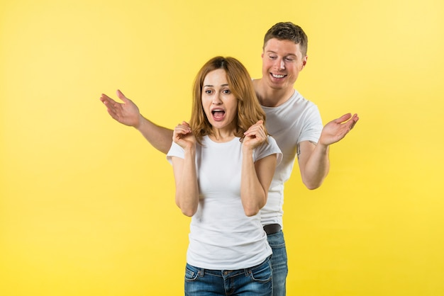 Smiling young man standing behind the shocked girlfriend against yellow background