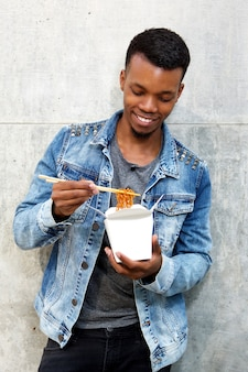 Smiling young man standing with box of noodles and chopsticks