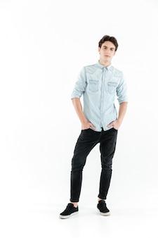 Улыбающийся молодой человек, стоя с руки в карманах