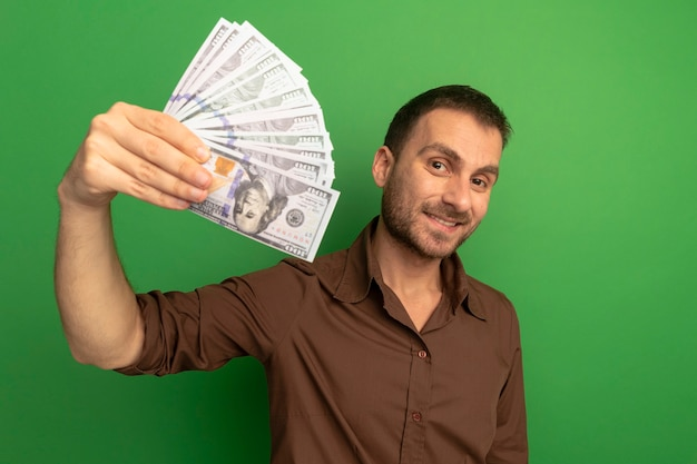 Smiling young man stretching out money towards front looking at camera isolated on green wall