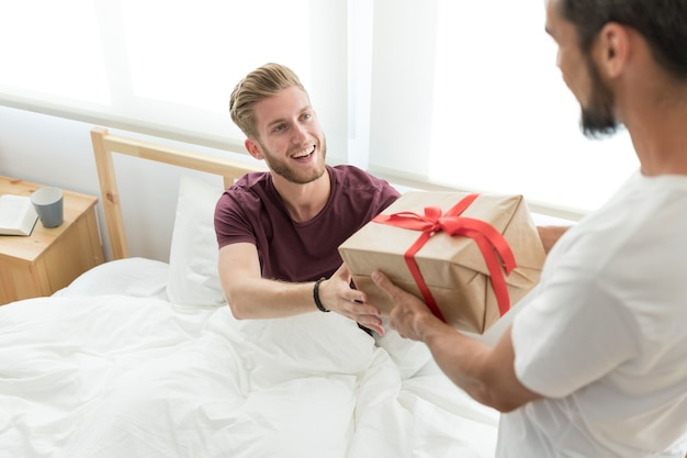 Smiling young man taking parcel from his friend