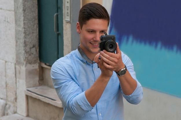 Smiling young man taking photo on camera in street