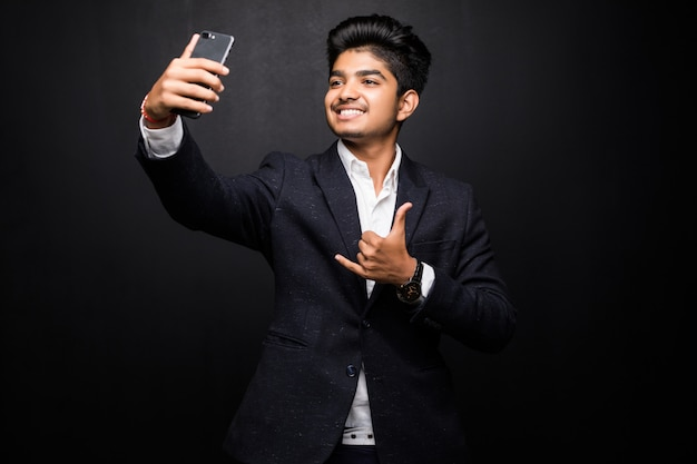 Smiling young man taking selfie photo on smartphone. indian guy using digital device. selfie photo concept. isolated front view on black wall.