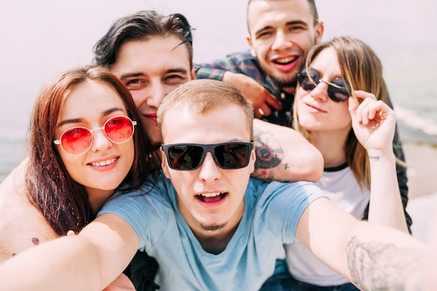 Smiling young man taking selfie with friends