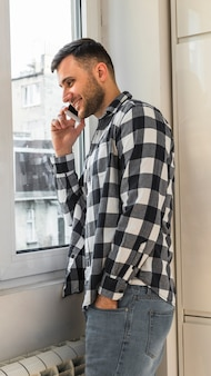 Smiling young man talking on mobile phone standing near the window