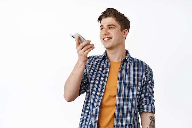 スピーカーフォンで話している笑顔の若い男、音声メッセージを録音するか、携帯電話アプリでスピーチを翻訳し、白の上にカジュアルに立っています。