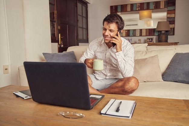 젊은 남자가 전화로 얘기하고 집에서 소파에 자신의 노트북 컴퓨터 앞에서 커피를 마시는 웃고. 그는 재택 근무를하고 흰색 셔츠와 반바지를 입습니다.