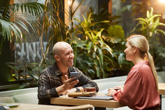 Улыбающийся молодой человек разговаривает с молодой женщиной за столом в кафе