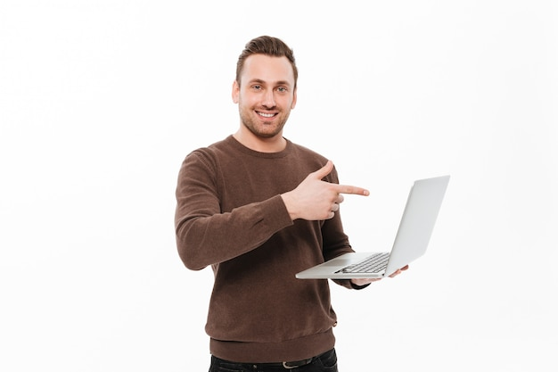 Smiling young man using laptop computer pointing.