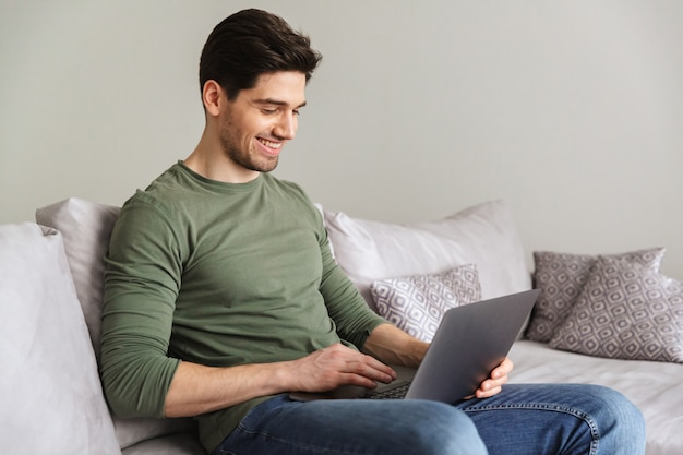 Улыбающийся молодой человек, используя портативный компьютер