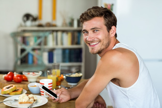Smiling young man using mobile phone at breakfast table