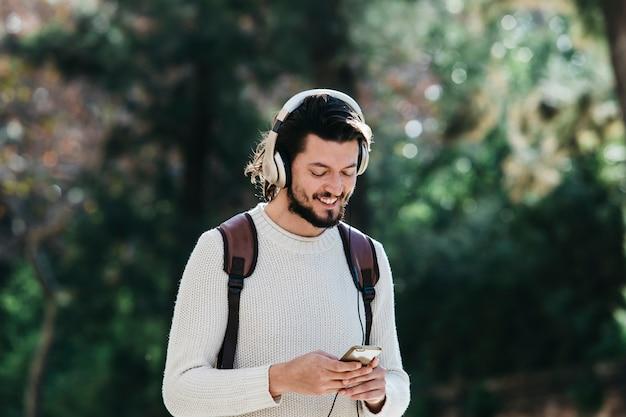 Улыбающийся молодой человек, используя телефон для прослушивания музыки на наушники в парке