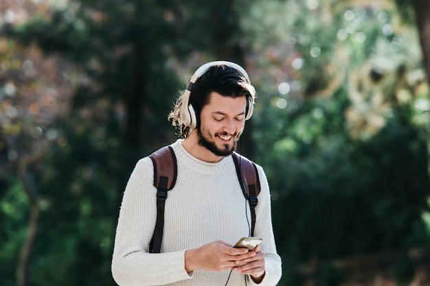 Smiling young man using phone for listening to music on headphone in the park