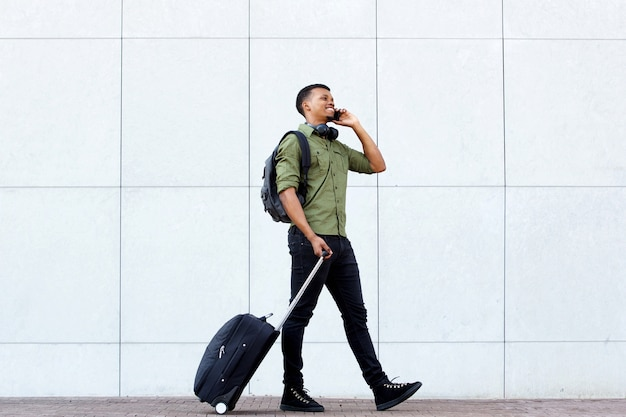 Smiling young man walking with luggage and mobile phone