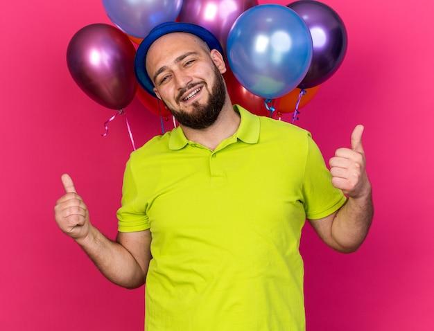 ピンクの壁に分離された親指を示す前の風船に立っている青いパーティー帽子をかぶって笑顔の若い男