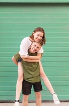 カジュアルな服を着て笑顔の若い男が彼の背中に幸せな女の子を着ています。