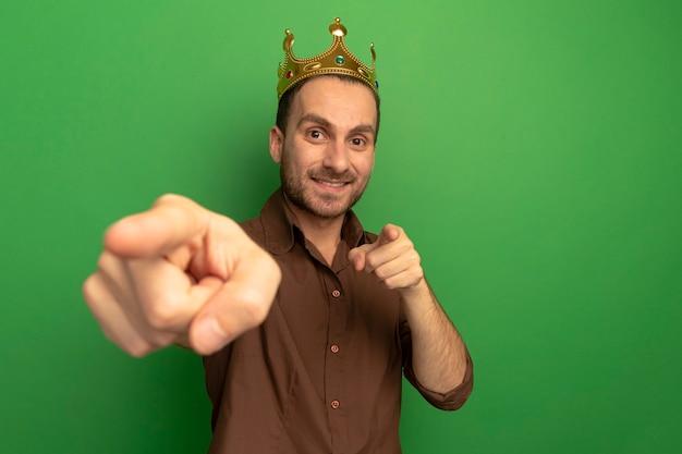 녹색 벽에 고립 된 제스처를 하 고 정면을보고 왕관을 쓰고 웃는 젊은 남자