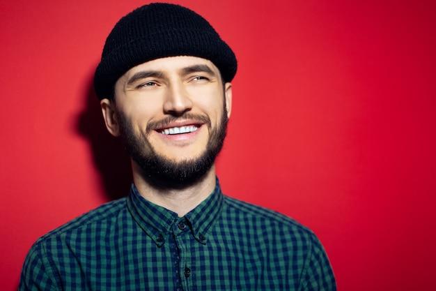 赤い壁に緑の格子縞のシャツと黒のビーニー帽子をかぶって、若い男を笑っています。