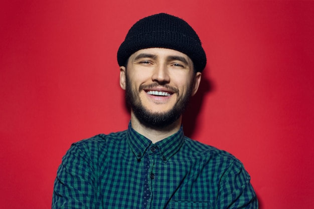 Smiling young man, wearing green plaid shirt and black beanie hat on red wall.