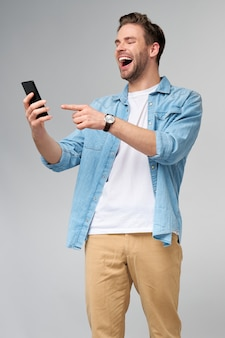 Smiling young man wearing jeans shirt taking selfie photo on smartphone or making video call standing