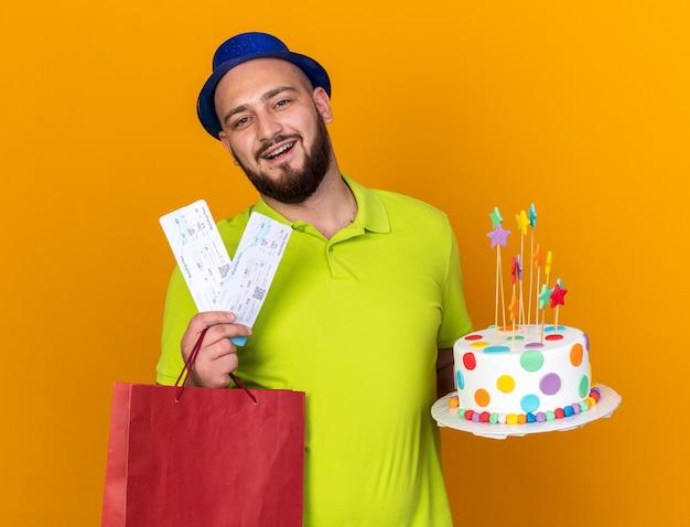 Улыбающийся молодой человек в партийной шляпе держит подарочный пакет с тортом и билетами, изолированными на оранжевой стене