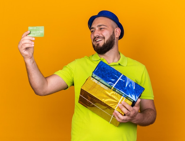Smiling young man wearing party hat holding gift boxes and looking at credit card in his hand