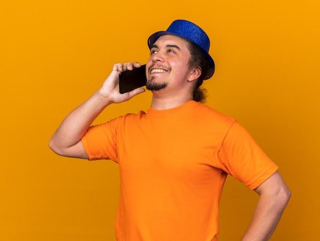 파티 모자를 쓰고 웃는 젊은 남자가 엉덩이에 손을 대고 전화로 말한다