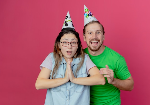 Smiling young man wearing party hat and surprised young girl holds hands together isolated on pink wall