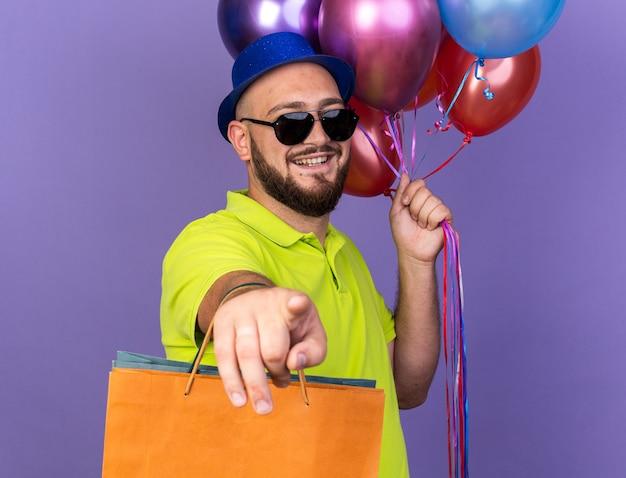 Улыбающийся молодой человек в партийной шляпе в очках держит воздушные шары с подарочным пакетом, показывая вам жест, изолированный на синей стене