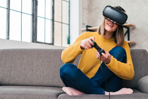 Smiling young man wearing virtual reality glasses sitting on sofa playing video game with joysticks