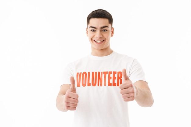 Улыбающийся молодой человек в футболке-добровольце стоит изолированно над белой стеной и показывает палец вверх